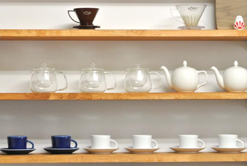 カウンター後方に陳列されたコーヒーカップやティーポット